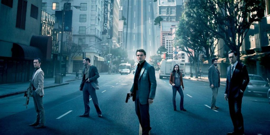 Characters in the film 'Inception' stand on a city street. Behind them, the street curves sharply upwards.