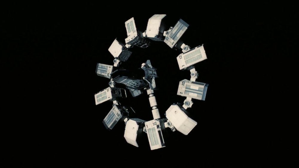 The Endurance space craft, composed of a station at the center surrounded by twelve stations in a circle like the twelve items of a clock. A corridor is connecting the center to one of the twelve stations like the hand of a clock. The Endurance spins, representing time going by.