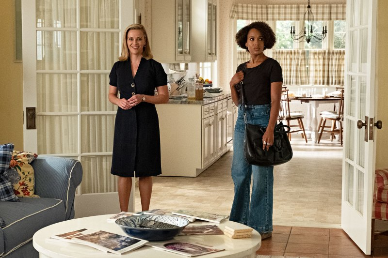 This image is from the TV Series Little Fires Everywhere. Two women stand in a living room. One, is smiling. The other looks uncomfortable.