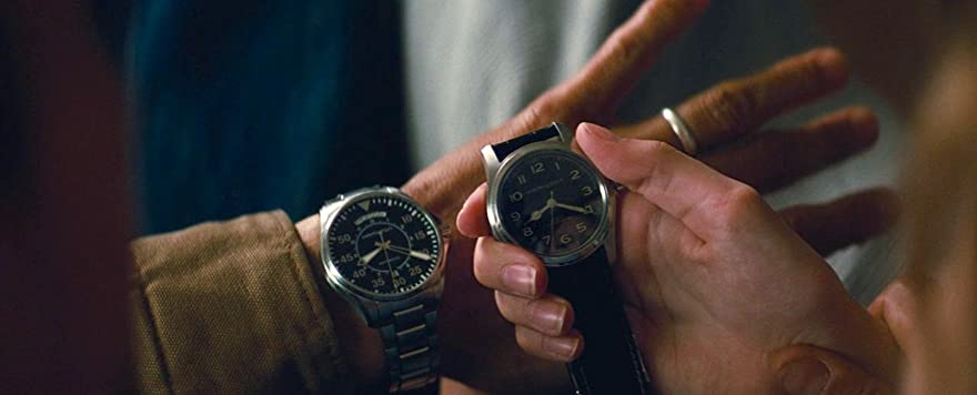 Cooper's watch is on his wrist, he has just given the other one to Murph, they are comparing them