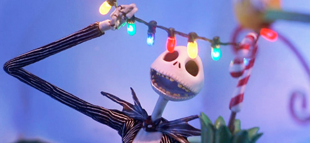 a claymation skeleton wearing a striped suit smiles at colorful string lights