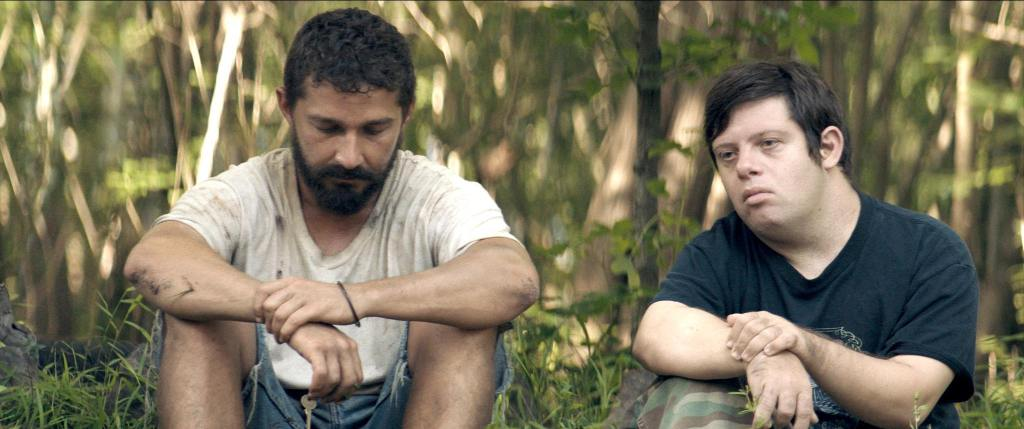 This is a still from the film Peanut Butter Falcons. Actor Shia LaBeouf is sitting down on the ground with actor Zack Gottsagen. There is a background of tree.
