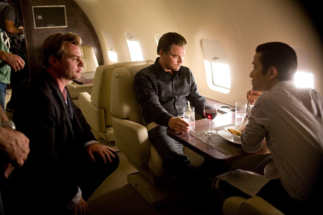 Christopher Nolan directing and talking with Leonardo DiCaprio and Joseph Gordon-Levitt on the set of Inception