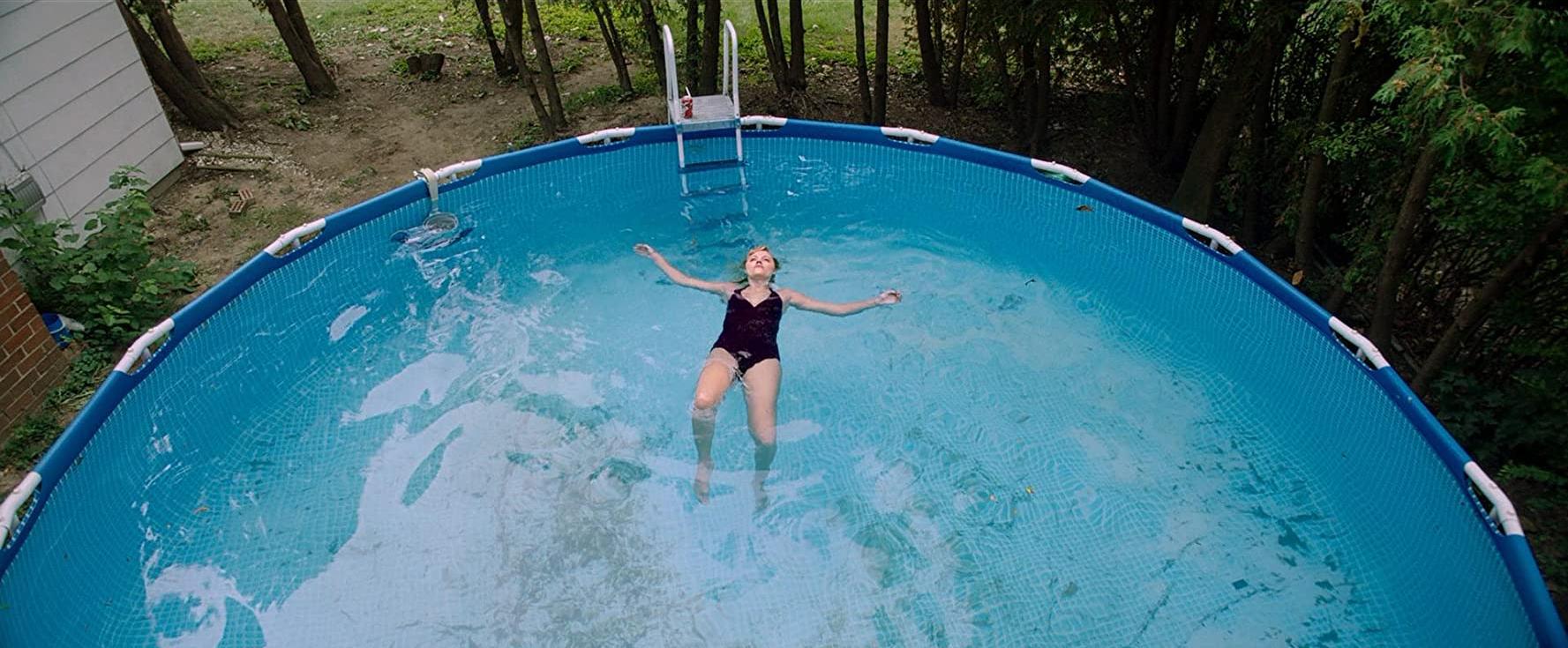 A girl in a black swimsuit lays on her back in a swimming pool.