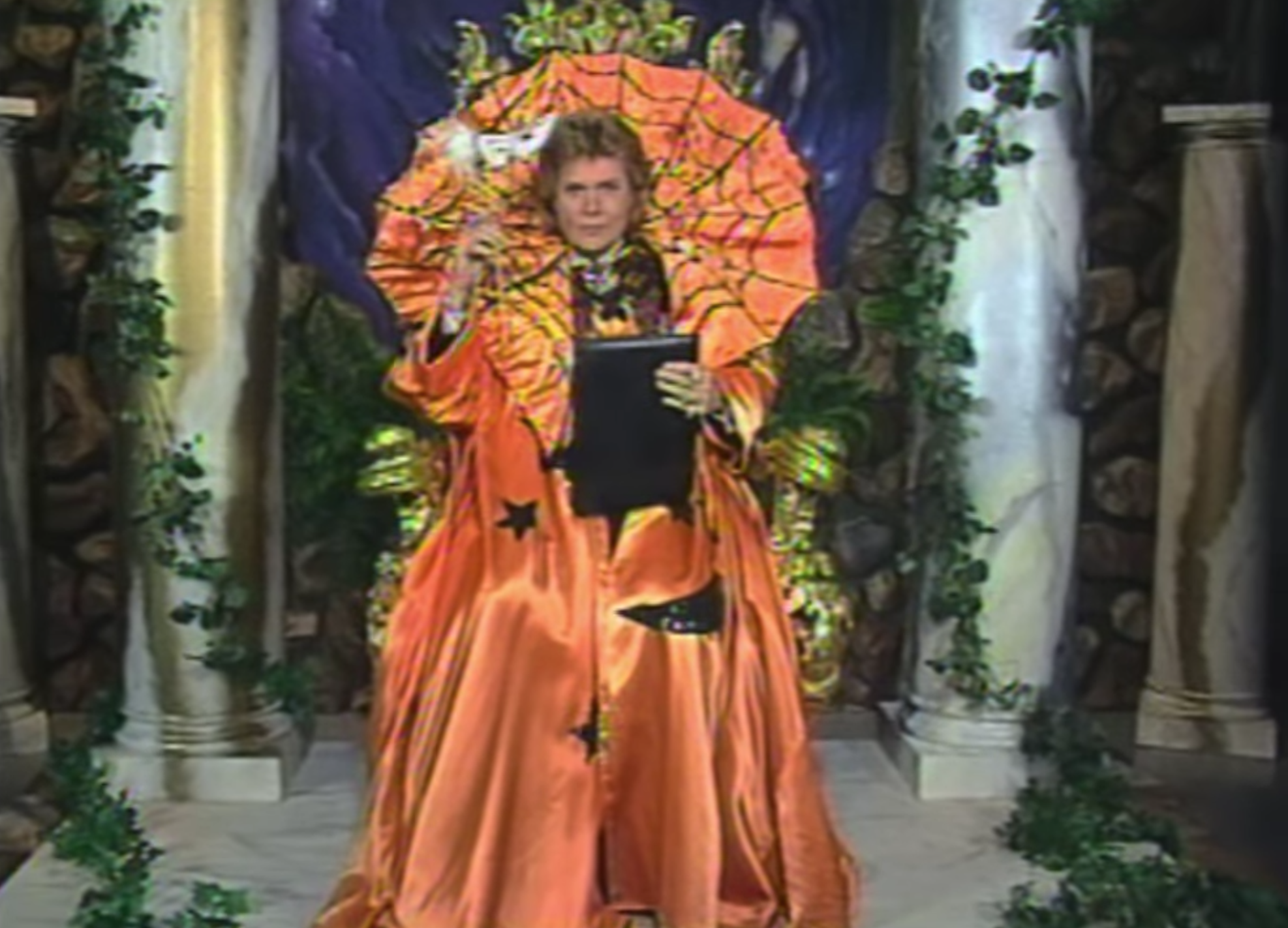 An old image from Walter Mercado's television program. Walter reads from a large book dressed in a huge orange cape decorated for Halloween. He looks like a large pumpkin.