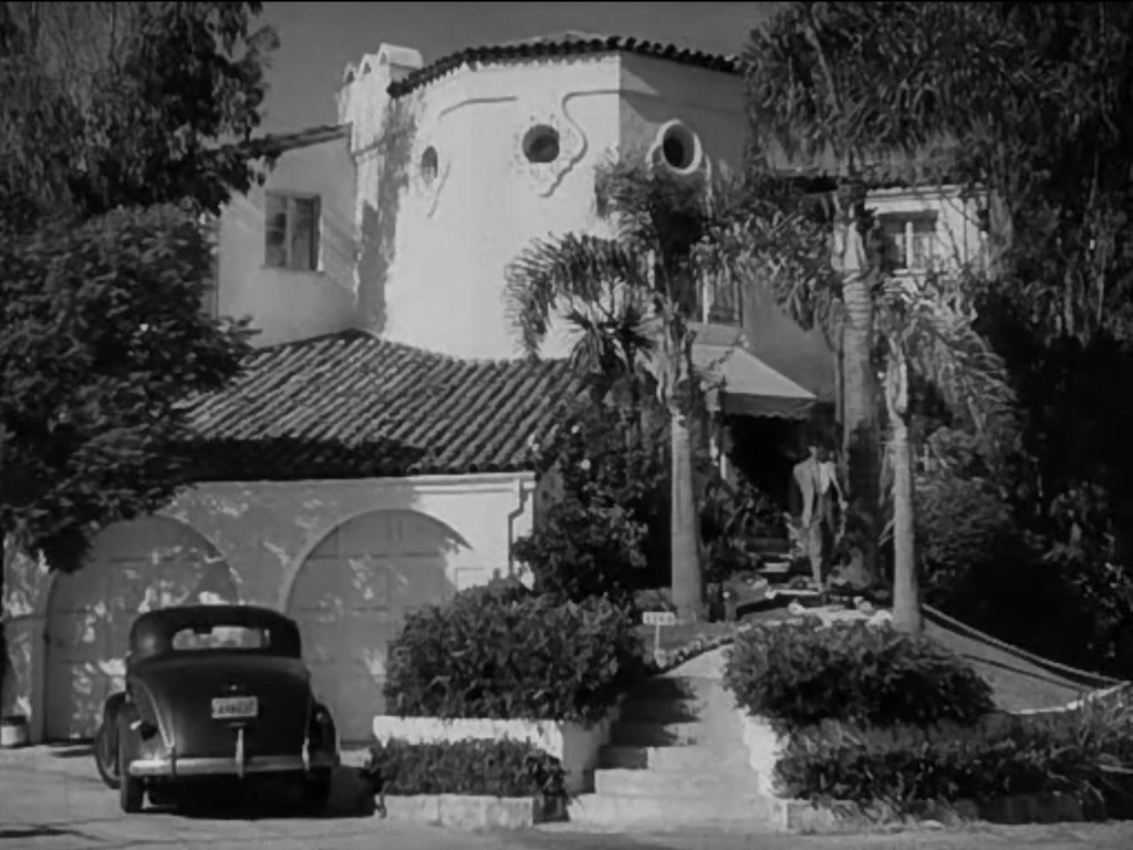 The Spanish-style house in Double Indemnity from the outside, with a car parked in the bottom left and Walter Neff walking down the steps.