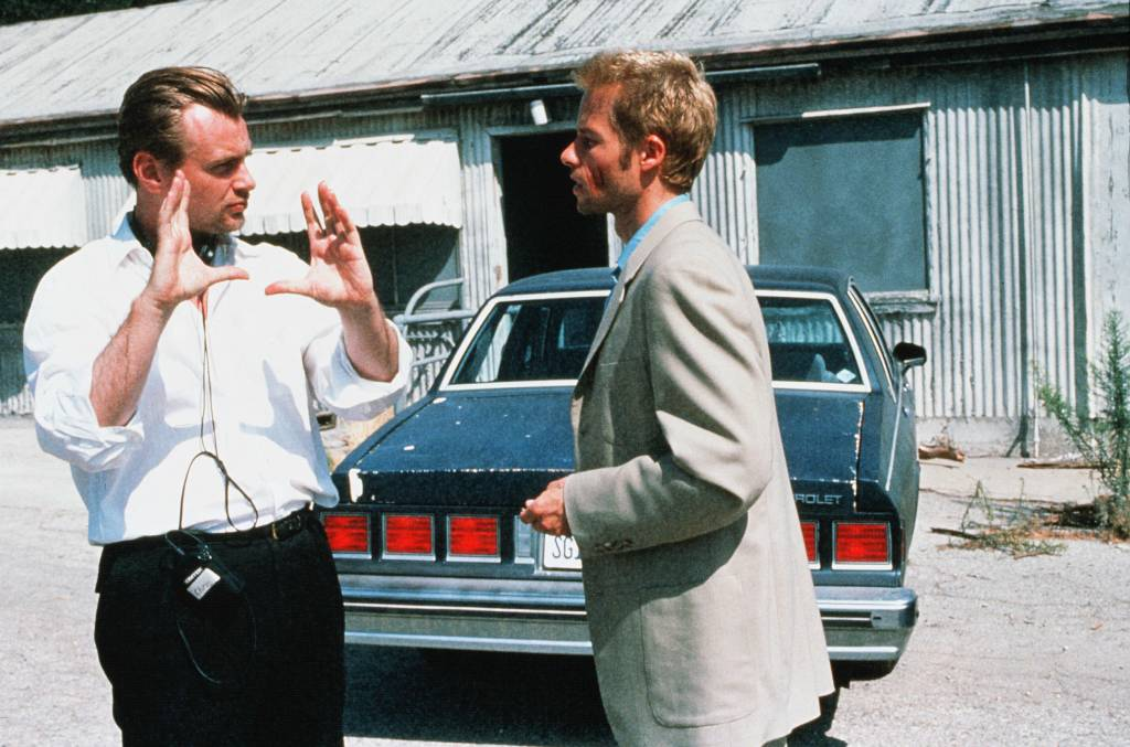 Christopher Nolan gesturing and directing Guy Pearse on the set of Memento
