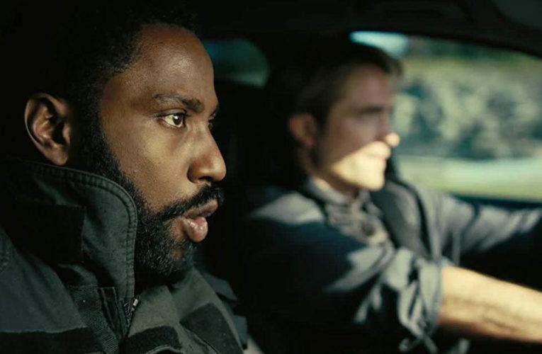 Actors John David Washington and Robert Pattinson in a car, a snapshot from Tenet's trailer