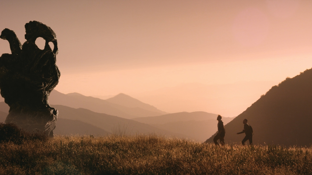 This image is from The Endless. Two men walk through a meadow and approach a skull-like statue.