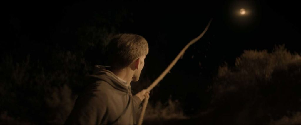 This image is from The Endless. Aaron looks up at a rope that leads up into the night sky and pulls it.