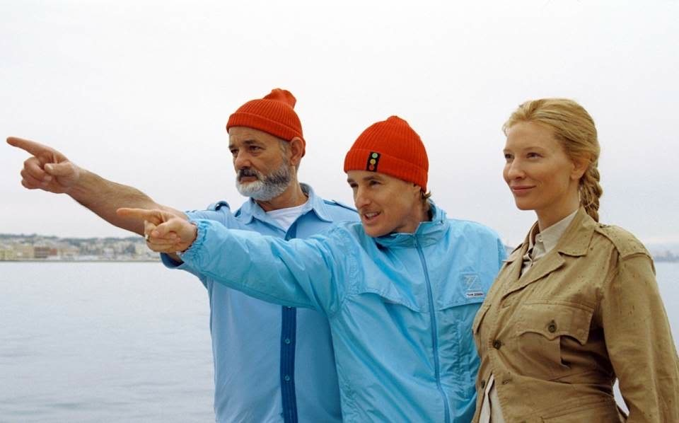 Screen capture from The Life Aquatic with Steve Zissou. Two men (Bill Murray and Owen Wilson) and a woman (Cate Blanchett) stood on a boat. The two men are pointing into the distance.