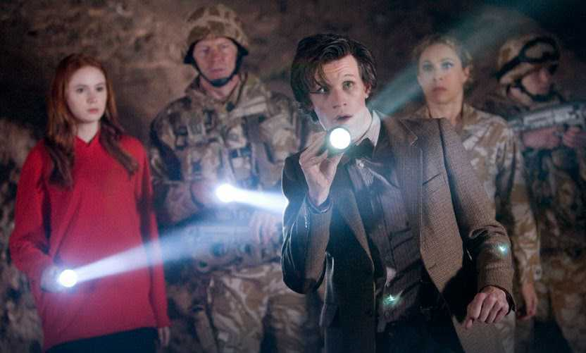 Inside a cavern in episode 'The Time of Angels' Amy, military-garbed Father Octavian, River Song, and a cleric watch nervously as The Doctor points a flashlight on something surprising in the distance