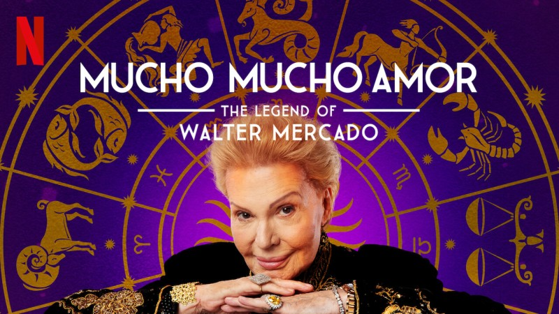 "Promotional photo for the Netflix documentary ""Mucho Mucho Amor: The Legend of Walter Mercado."" An image of Walter Mercado's smirking face over an astrological wheel."