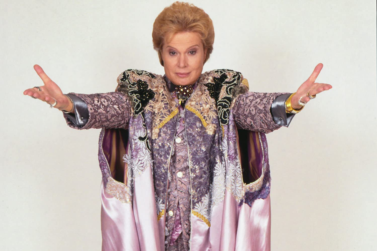 Walter Mercado stands arms spread out presenting himself. He wears an extravagant purple robe with intricate design.