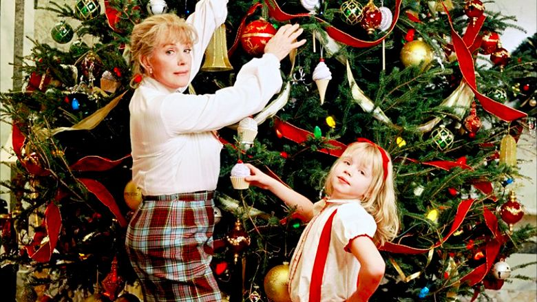 Nanny and Eloise stand in front of a massive Christmas tree decorated with ribbon, sphere ornaments, and cupcake ornaments