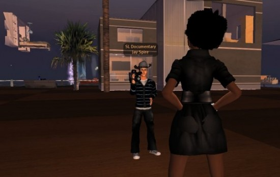 Image shows two avatars inside the game Second Life, one of whom is filming the other.