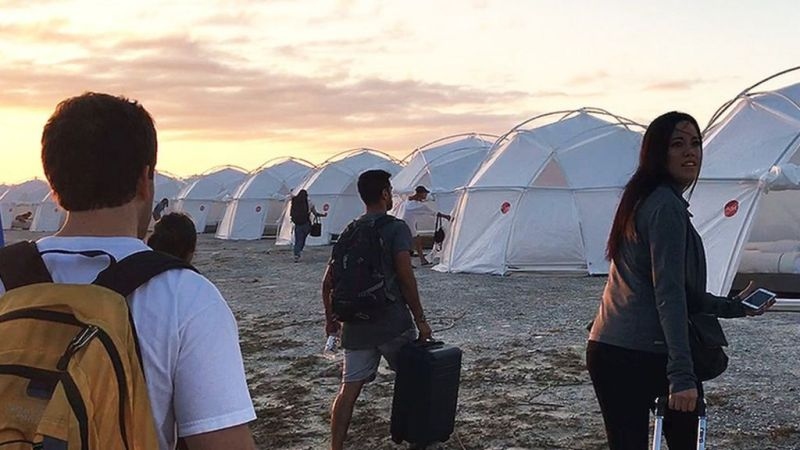 Image from the Netflix film Fyre: The Greatest Party That Never Happened. Influencers attending the festival walk towards a series of domed white tents, looking shocked.