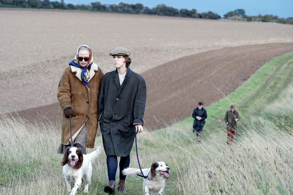 Image from The Souvenir. Two women walk their dogs in a field. Two men follow them in the distance.