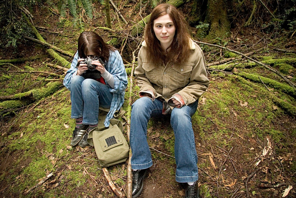 Image from We Go Way Back. Young Kate and Older Kate sit on a small hill in a forest. Young Kate is taking pictures, whilst Older Kate is watching something in the distance.