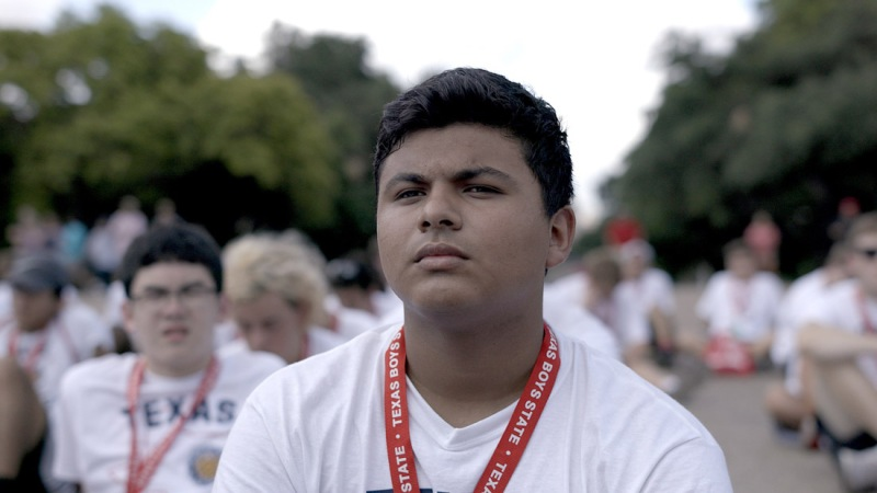 A close up of a teenager boy, who is sat amongst others wearing the same white Texas shirt and red lanyard.