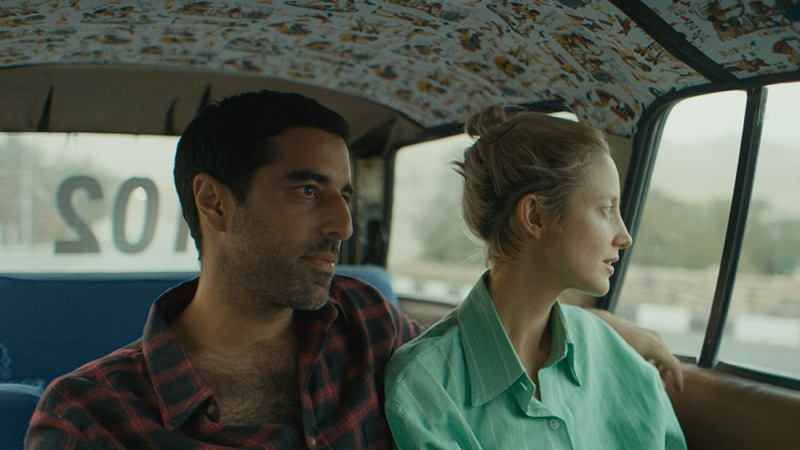 Sultan and Hana sit in the back of a car. Sultan has his arm around her.