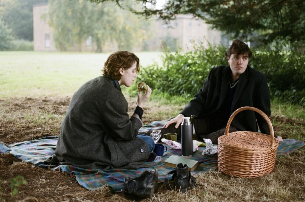 Image from The Souvenir. A couple are having a picnic in a park.