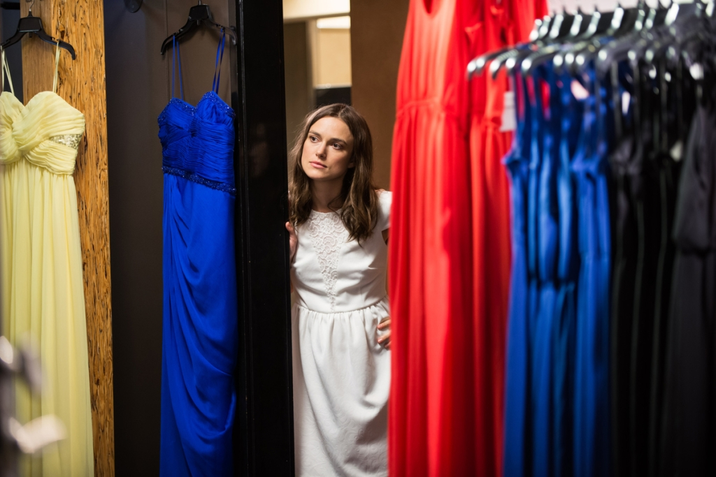 Image from the film Laggies. Megan looks round the corner of a dressing room. She is wearing a white dress.