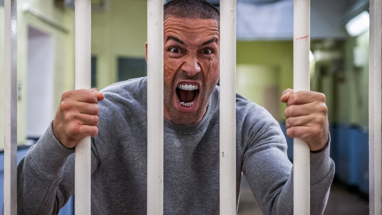 This image is from the film Avengement (2019). A man holds on to the bars of a jail cell and screams.