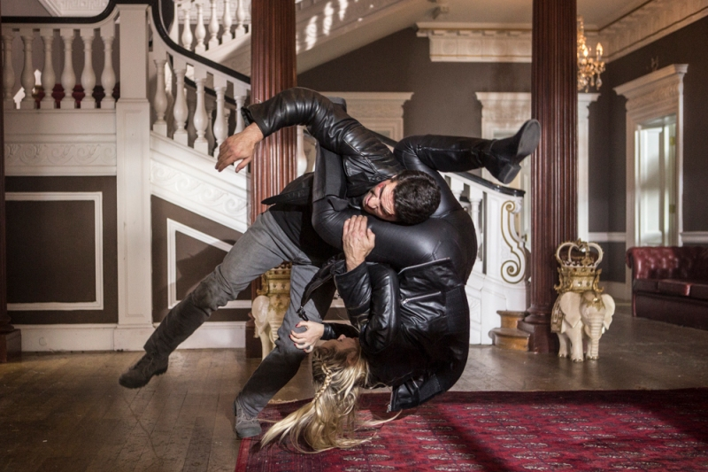 This image is from Accident Man (2018). A man and a women are mid somersault, with the women's legs around the man's neck, as they fight one another.