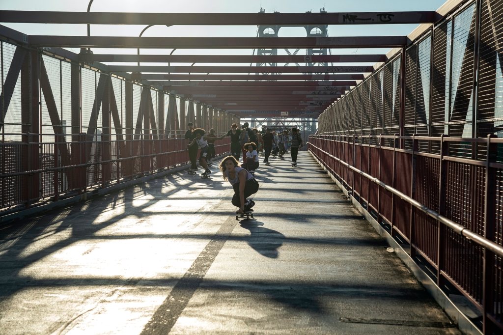 A large group of people skate across a bridge.