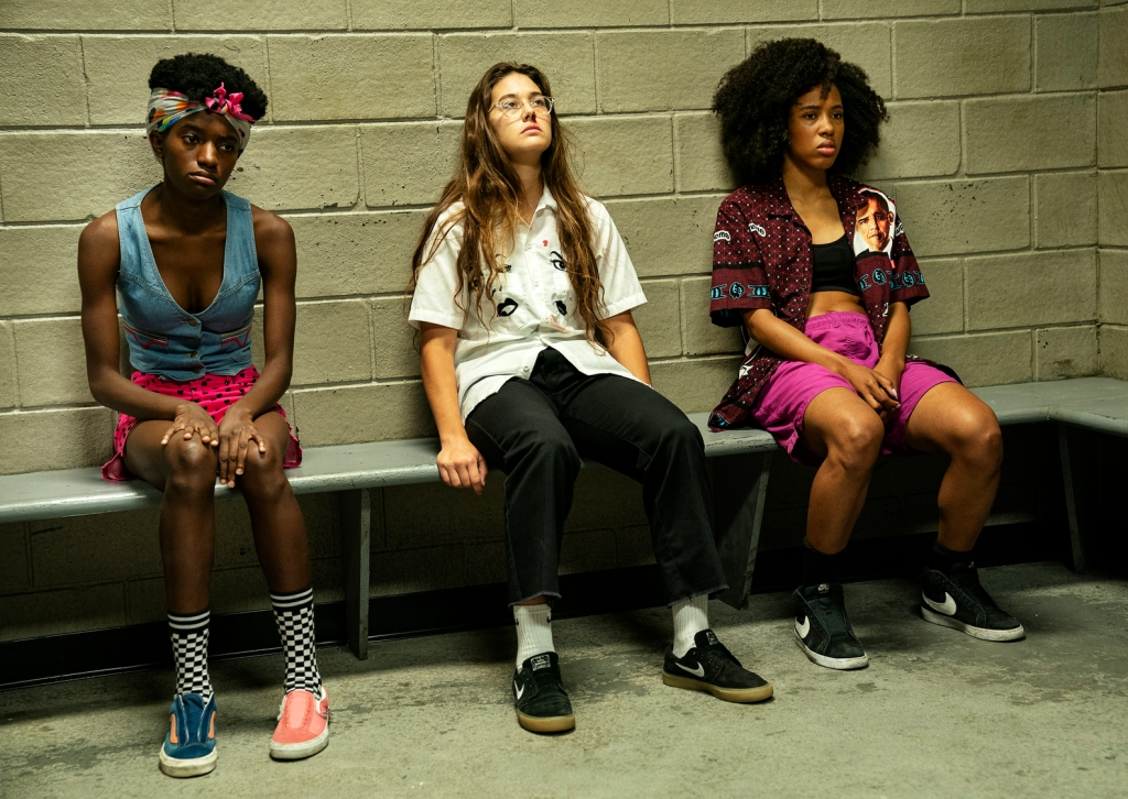 Janay, Honeybear and Camille sit with their backs against a white brick wall. They are in a jail cell.