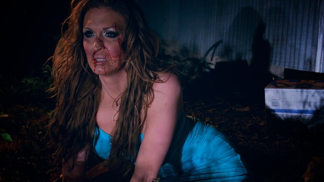 A woman in a blue dress with long brown hair, shiny eyeshadow, and blood splattered across her face sits on the ground with a look of fear