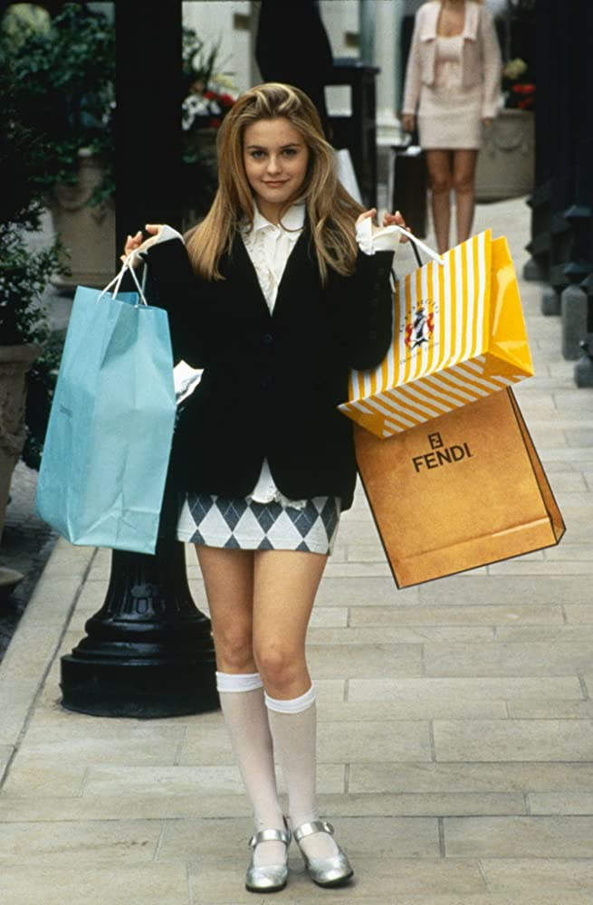 Alicia Silverstone as Cher proudly displaying bags from designer brands.