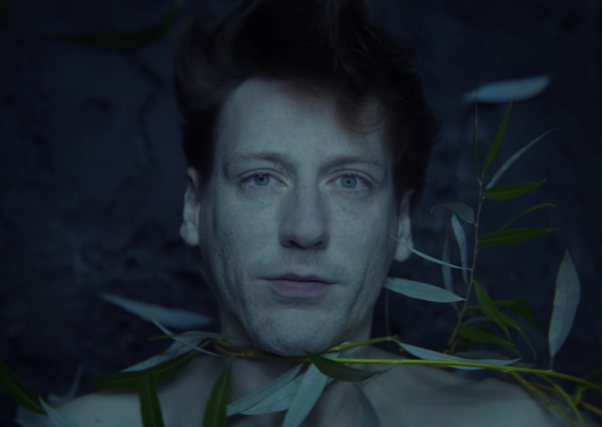 A man looks directly at the camera as he floats underwater. Several vines cover