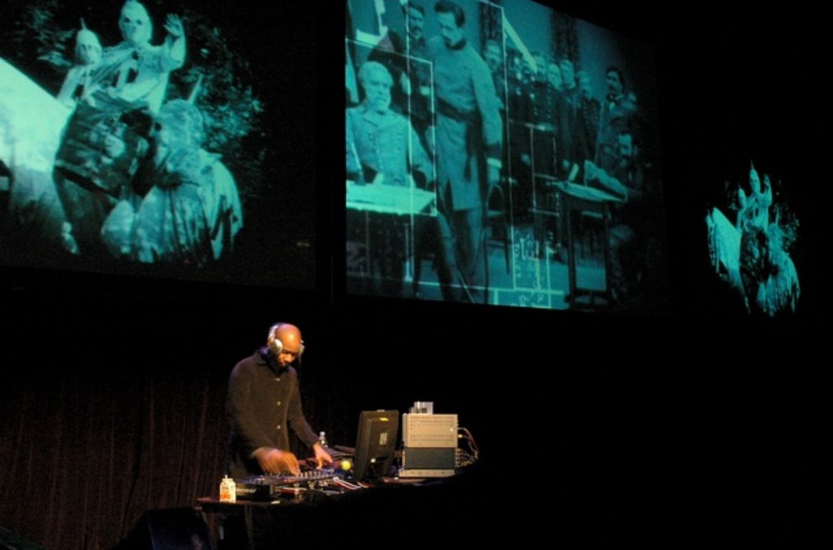 Image shows DJ Spooky performing in front of three large screens.