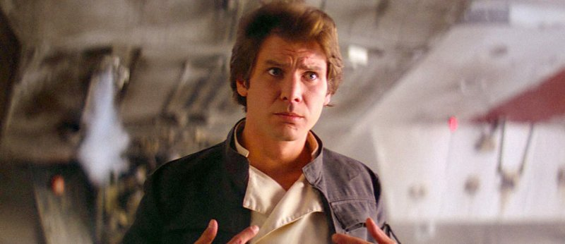Han Solo stands in front of the Millenium Falcon pointing at himself quizzically in this frame from The Empire Strikes Back