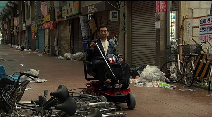 A character moves his mobility scooter through a deserted shopping street in Tokyo