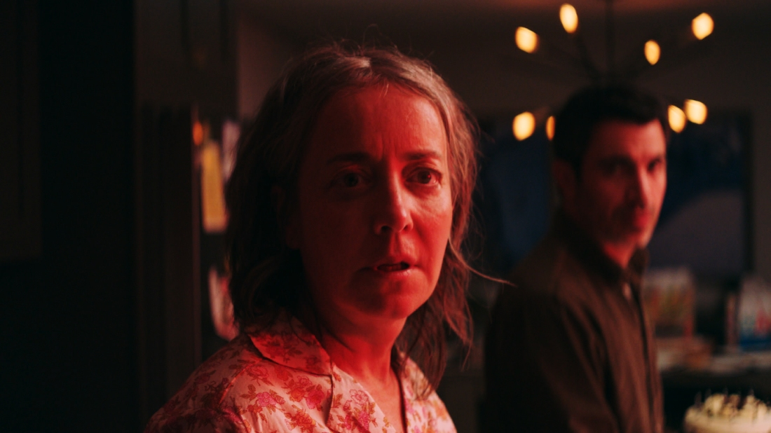 Jane (Jane Adams) in her pajamas, bathed in red light. Jason (Chris Messina) stands behind her.