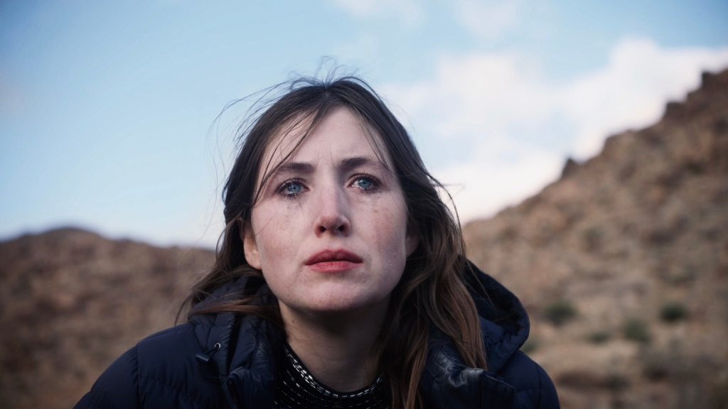 With a tear streaked face, Amy (Kate Sheil) sits up in the dessert.