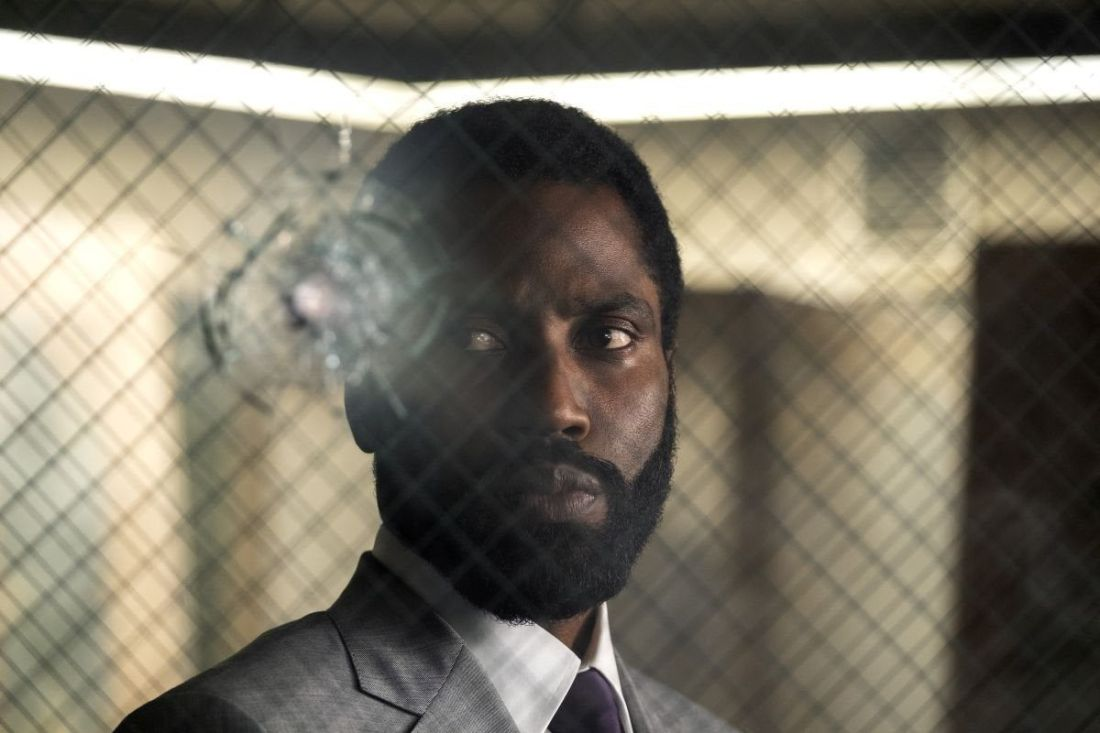 The Protagonist (John David Washington) stares at a glass bullet hole.