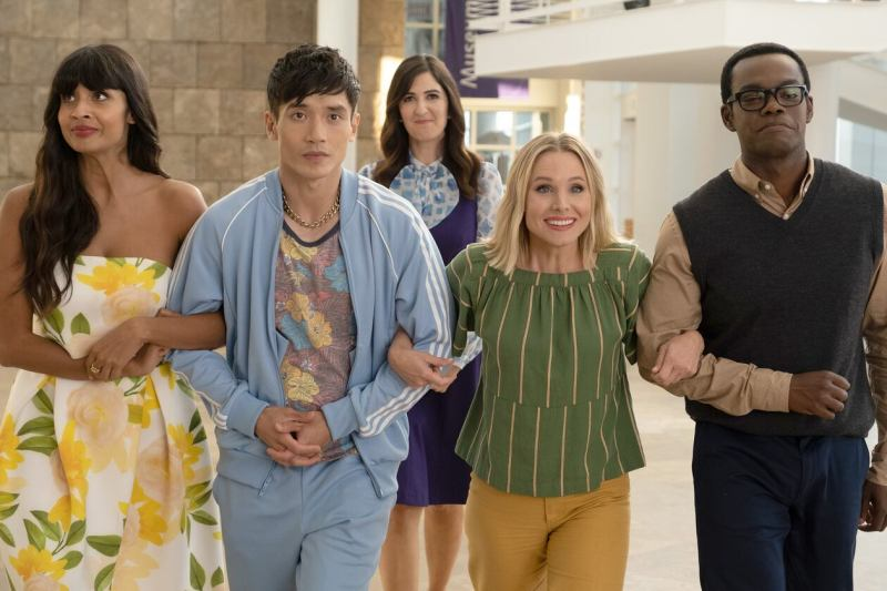 This image is from the TV Show The Good Place. Tahani, Jason, Eleanor and Chidi link arms and walk together. Janet is stood behind them, smiling.