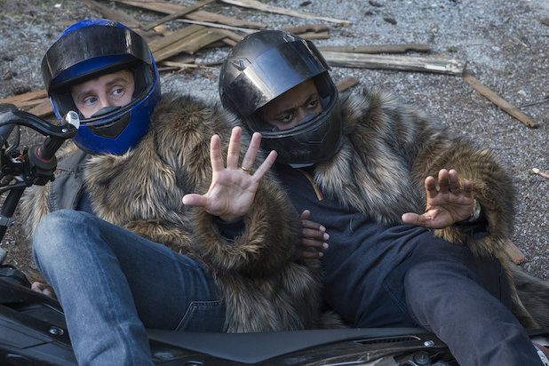 Roday Rodriguez and Hill as Shawn and Gus, lying on the ground dressed in fur coats and motorcycle helmets.
