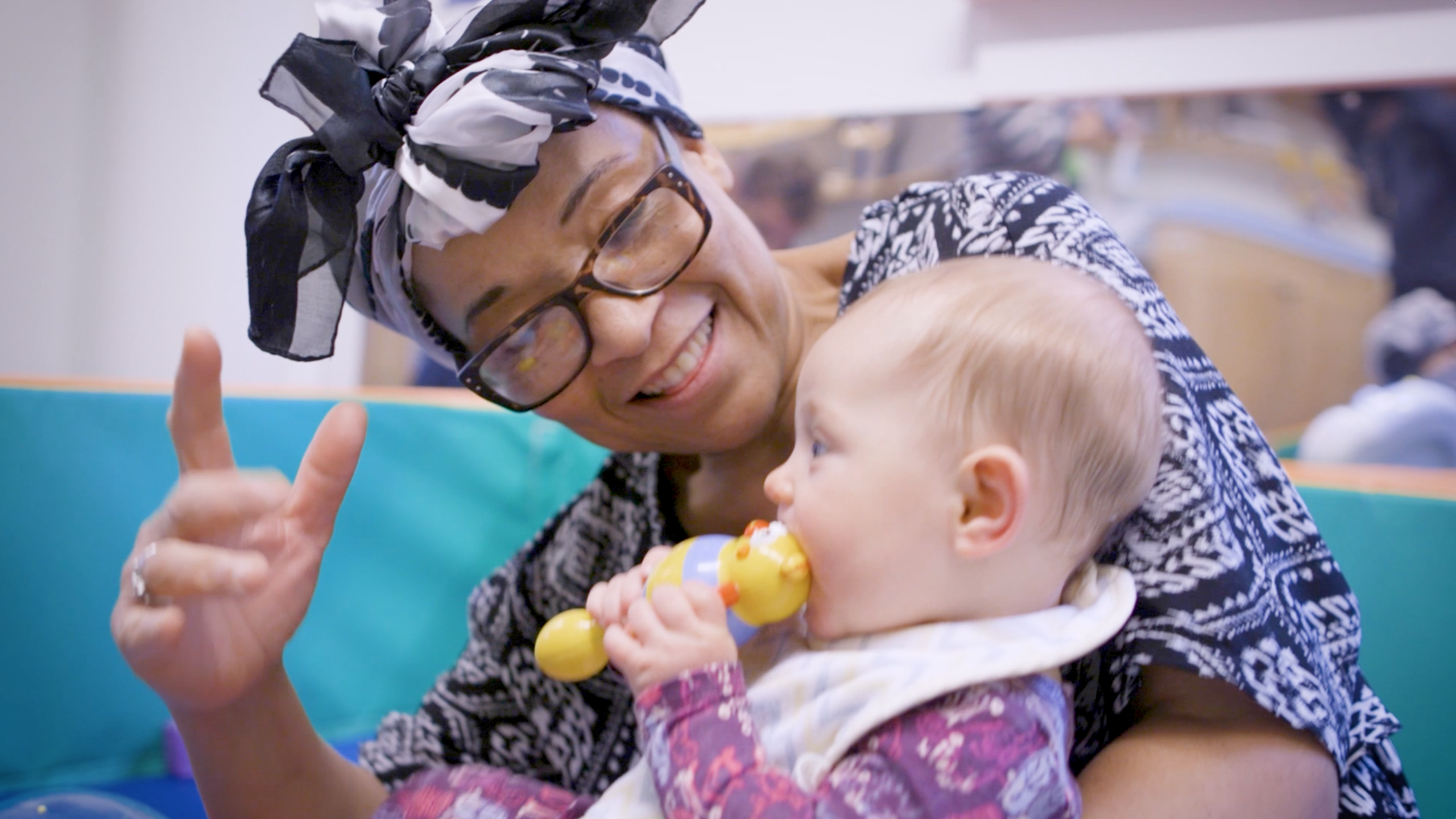 A woman holds a baby in her arms and plays with her.