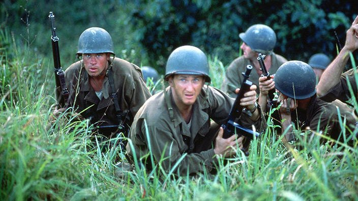 A group of soldiers sit poised in the grass, looking anxiously alert, in this image from The Thin Red Line