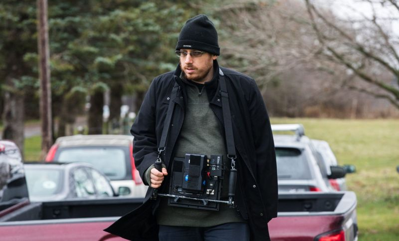 Director Justin McConnell stands at centre frame with a sound machine around his neck.