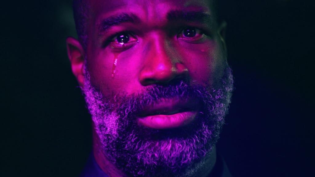Brian (Tunde Adebimpre) sheds a tear against a black backdrop.