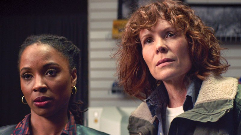 "Two women look past the camera at someone, on the right is a red-haired White woman in ""butch"" clothing and next to her is a shorter Black woman with black hair that is pulled back. She is wearing earrings and a collared shirt."