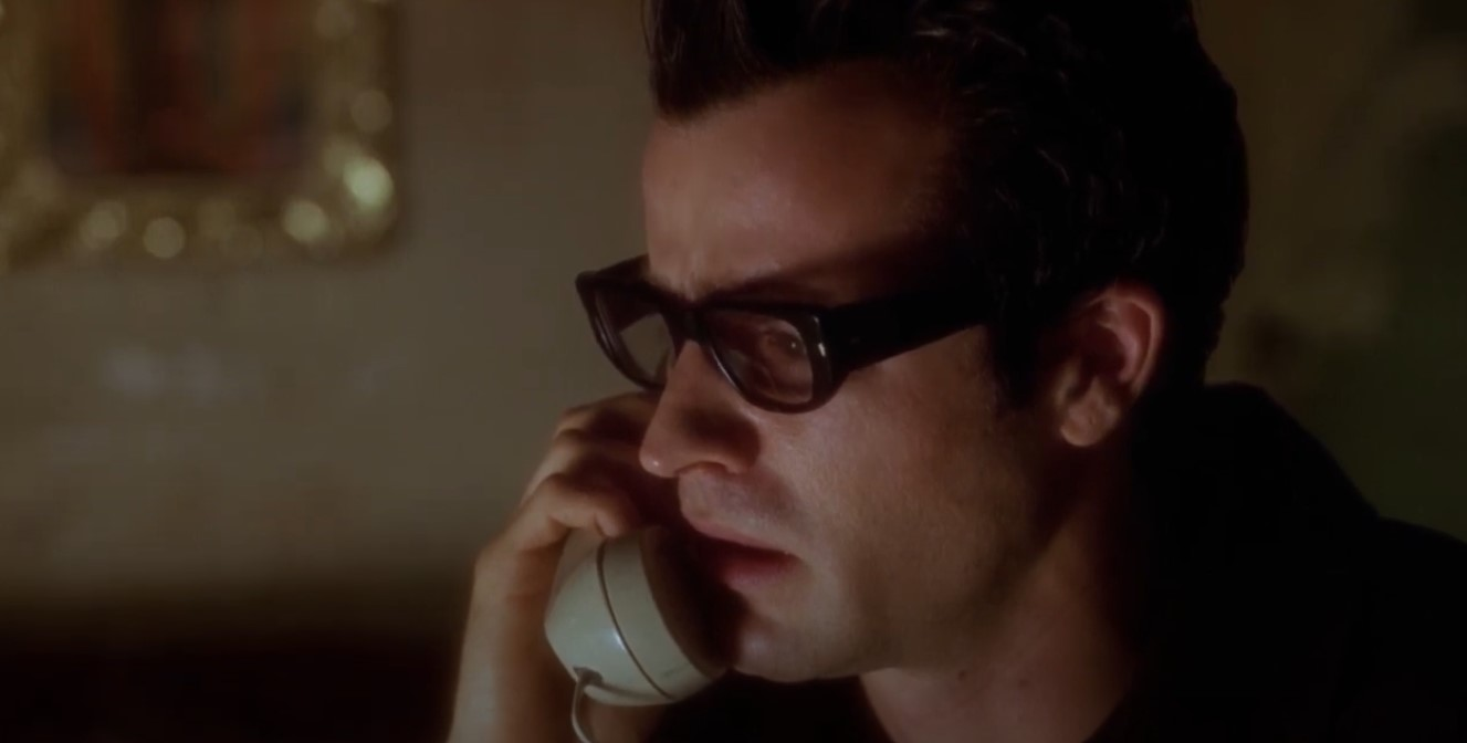 Image from the film Mulholland Drive. A man is on the phone in a dimly lit room.
