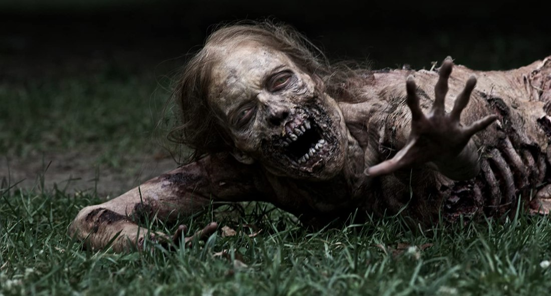 Image still from the first episode of The Walking Dead. A rotting zombie crawling along the grass.