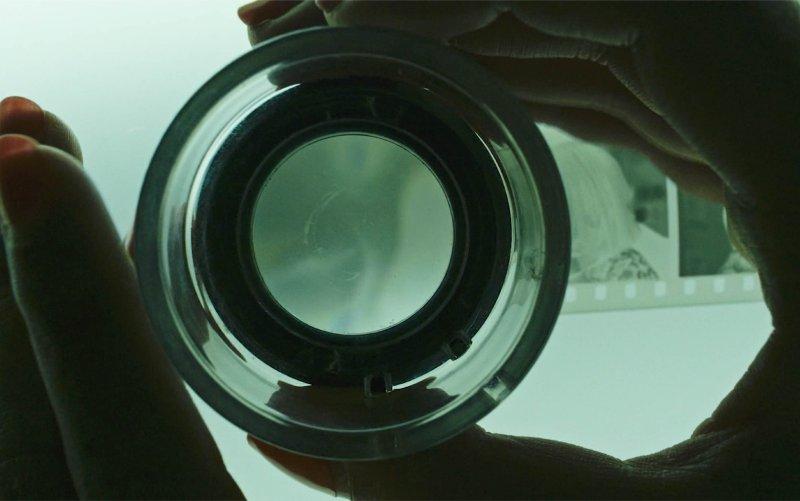 A closeup of Romvari's fingers as she looks at photo negatives.